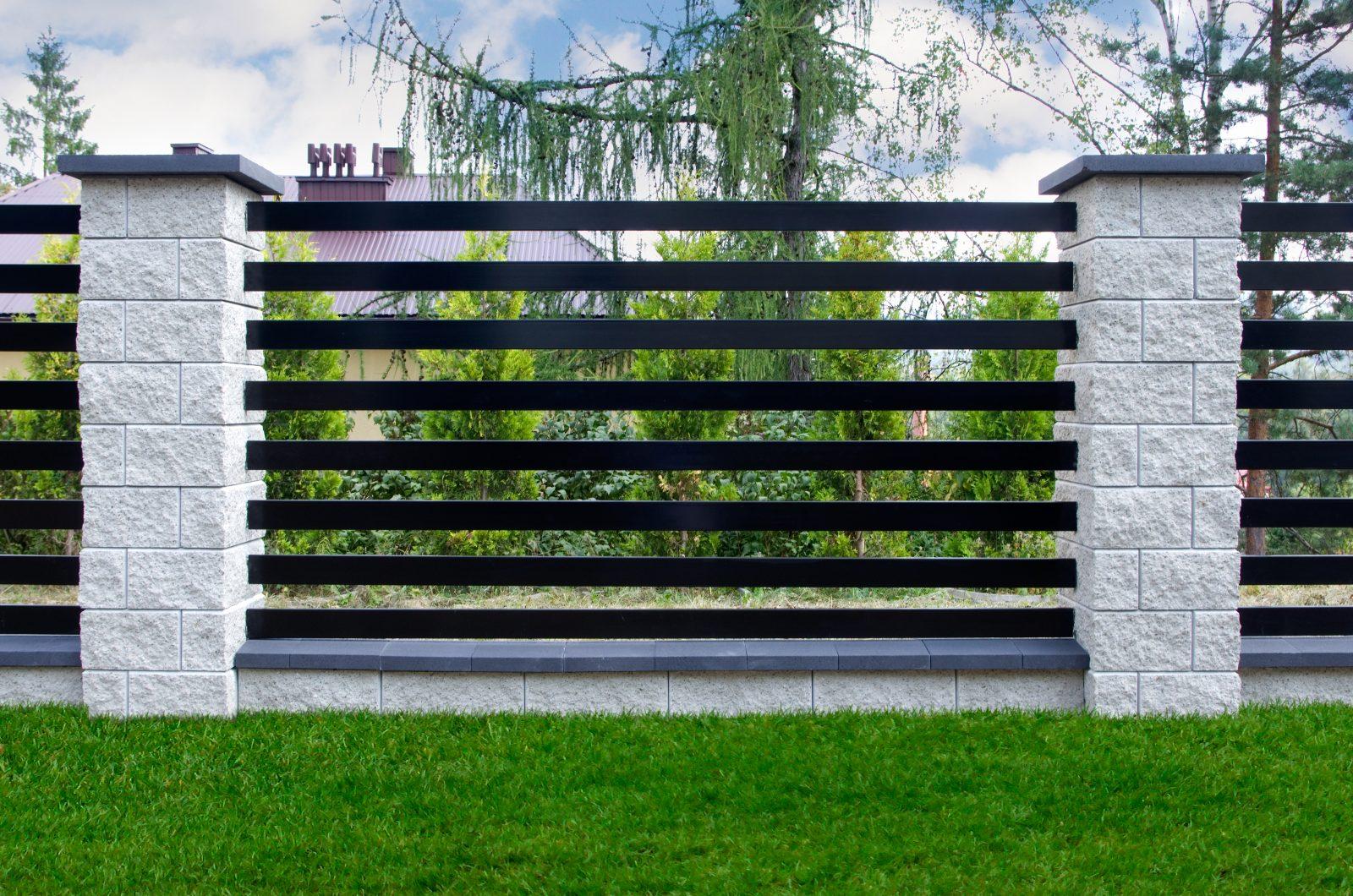 profile metalowe umieszczone jako palisada w płocie betonowym